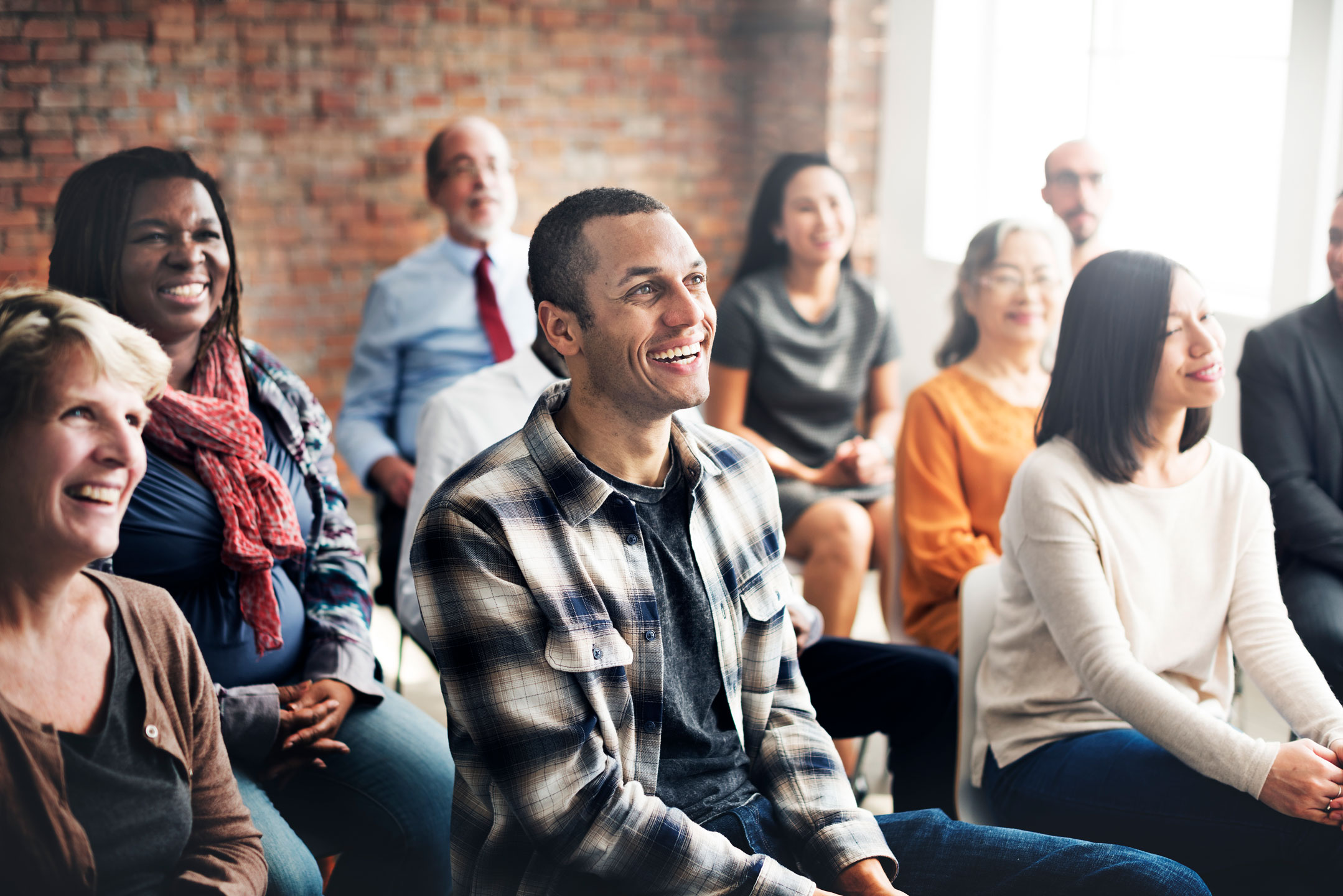 Education photo of group of people listening to a presentation and smiling