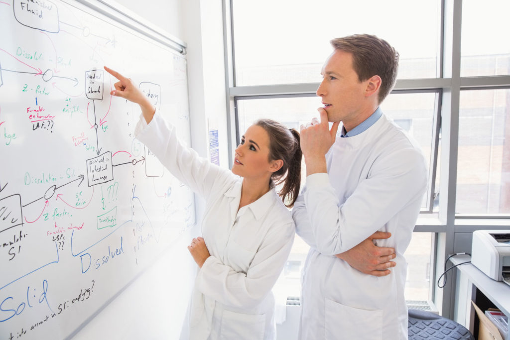 Research photo of woman and man in lab coats brainstorming on white board