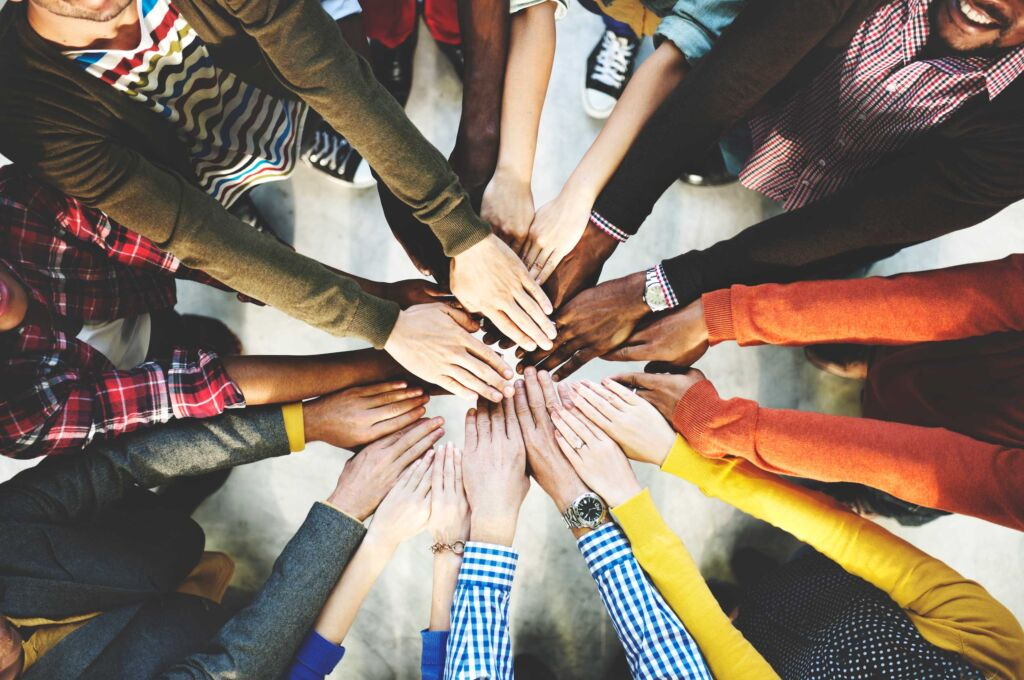 "Employees in a circle with both hands outstretched to be ""all in"" in a team huddle"